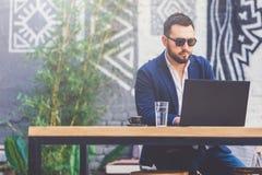 Retrato do homem de negócios que usa o portátil e sentando-se na tabela no café fotos de stock royalty free