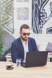 Retrato do homem de negócios que usa o portátil na tabela no café fotos de stock