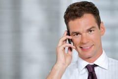 Retrato do homem de negócios que usa o telefone celular no escritório Foto de Stock