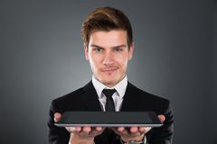 Retrato do homem de negócios seguro que guarda a tabuleta digital Imagens de Stock Royalty Free