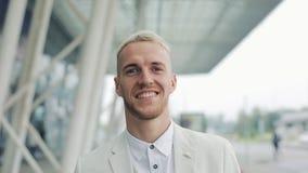 Retrato do homem de negócios de sorriso feliz considerável que anda perto do prédio de escritórios e que olha na câmera Vista do  filme
