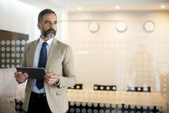 Retrato do homem de negócios superior com a tabuleta no escritório Fotos de Stock