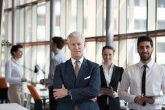 Retrato do homem de negócios superior como o líder com grupo de pessoas mim Imagens de Stock
