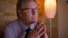 Retrato do homem de negócios superior na camisa que senta-se na frente da notícia de observação da tevê que é atenta e concentrad vídeos de arquivo