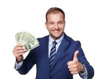 Retrato do homem de negócios considerável que mostra o fã dos dólares do dinheiro isolado Imagem de Stock