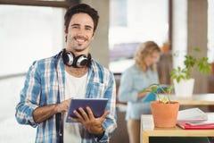 Retrato do homem de negócios feliz que guarda o escritório criativo da tabuleta digital Imagens de Stock Royalty Free
