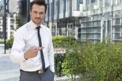 Retrato do homem de negócios irritado que mostra o dedo médio fora do prédio de escritórios Fotos de Stock