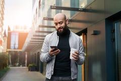 Retrato do homem de sorriso novo que usa o smartphone na rua da cidade O homem envia a mensagem de texto, bebe o café lifestyle R imagem de stock