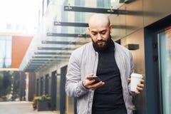 Retrato do homem de sorriso novo que usa o smartphone na rua da cidade O homem envia a mensagem de texto, bebe o caf? lifestyle R imagens de stock