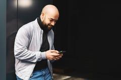 Retrato do homem de sorriso novo que usa o smartphone na rua da cidade O homem envia a mensagem de texto lifestyle Redes sociais fotografia de stock royalty free