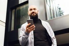 Retrato do homem de sorriso novo que usa o smartphone na rua da cidade O homem envia a mensagem de texto lifestyle Redes sociais fotos de stock royalty free
