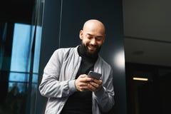 Retrato do homem de sorriso novo que usa o smartphone na rua da cidade O homem envia a mensagem de texto lifestyle Redes sociais fotos de stock