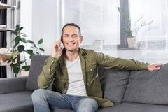 retrato do homem de sorriso que fala no smartphone ao descansar no sofá fotografia de stock