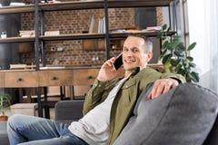 retrato do homem de sorriso que fala no smartphone ao descansar no sofá imagem de stock royalty free