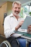 Retrato do homem deficiente na cadeira de rodas usando a tabuleta de Digitas em H foto de stock royalty free