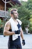 Retrato do homem desportivo com toalhas e garrafa da água. fotografia de stock royalty free