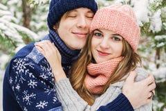 Retrato do homem e da mulher de abraço na floresta do inverno entre o abeto t Imagens de Stock Royalty Free