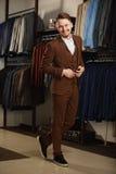 Retrato do homem elegante bonito novo contra a sala de exposições, tentando na roupa, levantando Foto da propaganda Imagem de Stock Royalty Free