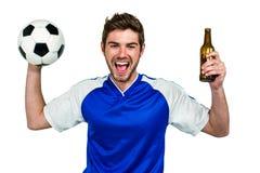 Retrato do homem entusiasmado que guarda o futebol e a garrafa de cerveja Fotografia de Stock