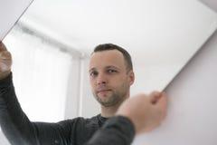 Retrato do homem europeu adulto novo com espelho imagem de stock