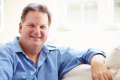 Retrato do homem excesso de peso que senta-se no sofá Fotos de Stock