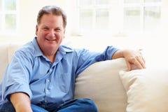 Retrato do homem excesso de peso que senta-se no sofá Imagem de Stock