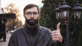 Retrato do homem farpado atrativo novo nos vidros e de olhar a câmera Homem com a cara de pôquer que faz os polegares acima video estoque
