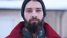 Retrato do homem farpado considerável que olha in camera o close-up Moscas grandes e impactos da bola de neve na cara de um homem vídeos de arquivo