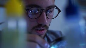Retrato do homem farpado novo bem sucedido no funcionamento de vidros com um ferro de solda em seu lugar de trabalho Conceito do filme