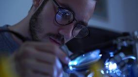 Retrato do homem farpado novo bem sucedido no funcionamento de vidros com um ferro de solda em seu lugar de trabalho Conceito do video estoque