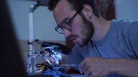 Retrato do homem farpado novo da habilidade no funcionamento de vidros com um ferro de solda em seu lugar de trabalho Conceito do filme
