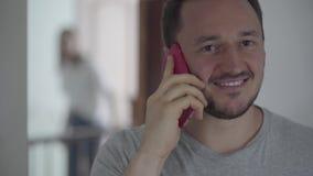 Retrato do homem feliz que fala com seu paramour pelo telefone celular quando sua esposa aparecer atrás e bisbilhotar filme