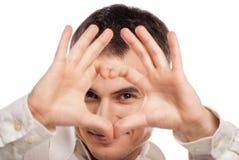 Retrato do homem feliz que faz o coração de suas mãos Fotos de Stock