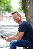 Retrato do homem feliz que senta-se no banco de parque com telefone celular fotografia de stock royalty free