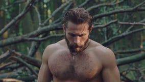 Retrato do homem forte agressivo na floresta lentamente filme