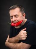 Homem idoso com pimenta vermelha em sua boca Foto de Stock