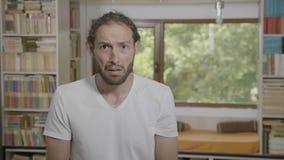Retrato do homem interessado novo que golpeia sua cara que gesticula o facepalm que expressa o embaraço e o forgetfulness - filme