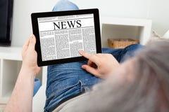 Retrato do homem maduro que usa a tabuleta de Digitas Fotografia de Stock Royalty Free