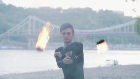 Retrato do homem magro novo que executa uma mostra com a posição do fã do fogo no riverbank na frente das árvores Fireshow hábil vídeos de arquivo