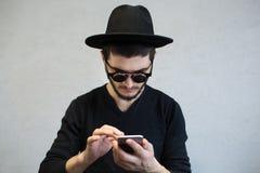 Retrato do homem no preto usando o smartphone com os óculos de sol no fundo branco fotos de stock royalty free