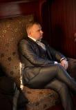 Retrato do homem no terno que levanta no sofá no trem retro Foto de Stock