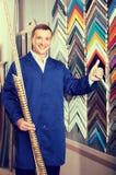 Retrato do homem no uniforme que escolhe moldar de quadro no estúdio Imagem de Stock
