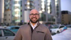 Retrato do homem novo à moda sério atrativo que olha na câmera e que sorri na cidade video estoque