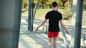 Retrato do homem novo apto com corda de salto na plataforma perto das cremalheiras do metal Exerc?cio de salto da aptid?o fora O  filme