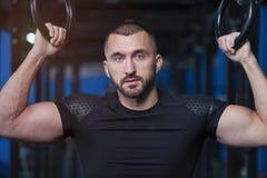 Retrato do homem novo atlético considerável com anéis da ginástica imagens de stock royalty free