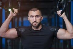 Retrato do homem novo atlético considerável com anéis da ginástica imagem de stock
