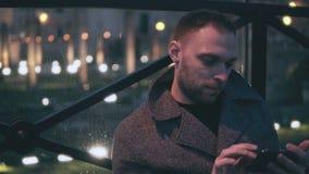Retrato do homem novo atrativo que senta-se na cidade da noite e no smartphone do uso O homem considerável consulta o Internet imagens de stock royalty free