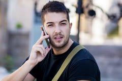 Retrato do homem novo bonito que fala no telefone exterior Foto de Stock