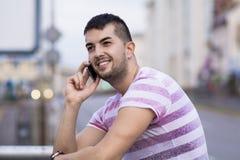 Retrato do homem novo bonito que fala no telefone exterior Fotos de Stock Royalty Free