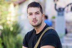 Retrato do homem novo bonito que senta-se na rua Imagens de Stock